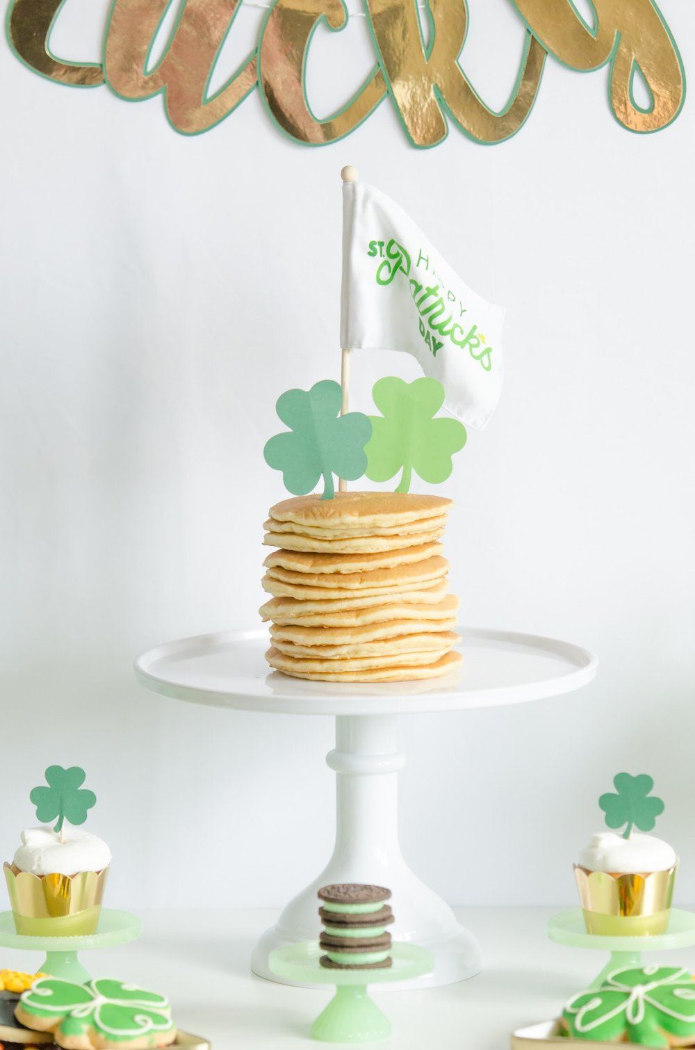 """Saint Patricks Day Breakfast Recipe: serve stacked pancakes on a cake stand, then add shamrock shaped cupcake toppers with a fun mini flag that says """"Happy St. Patrick's Day"""". Via Mint Event Design www.minteventdesign.com #partyideas #partydecorations #breakfastfood #saintpatricksday #stpatricksday #pancakes"""