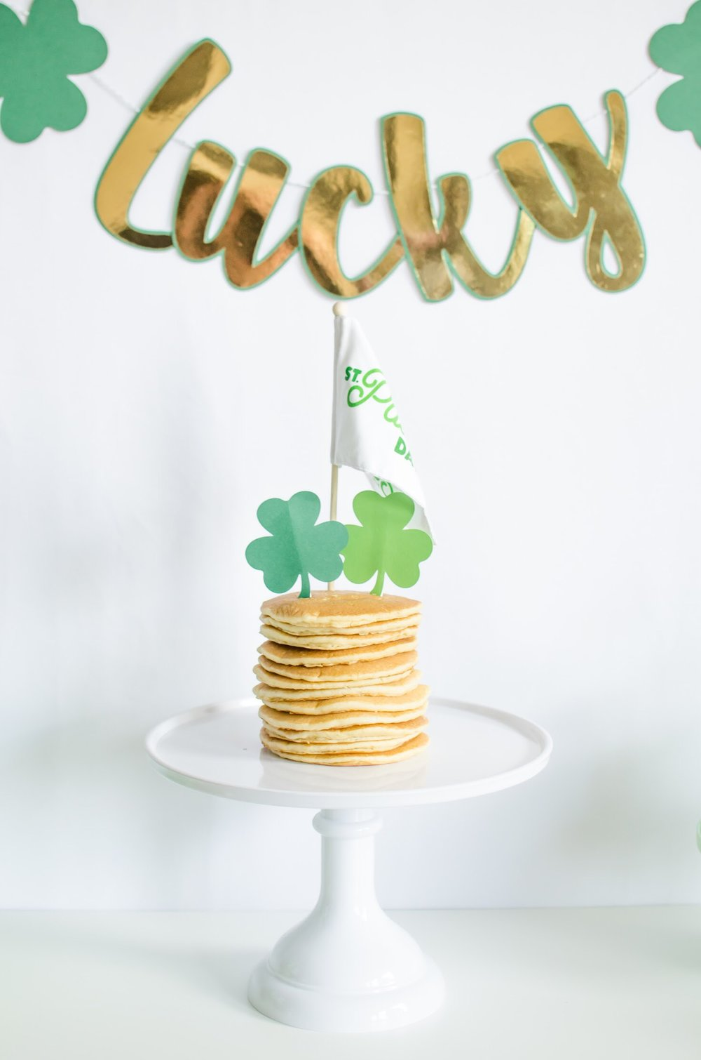Stacked Pancakes with shamrocks and a flag on top are the perfect breakfast choice for Saint Patricks Day. See all the green party details on Mint Event Design www.minteventdesign.com #partyideas #partydecorations #breakfastfood #saintpatricksday #stpatricksday #pancakes