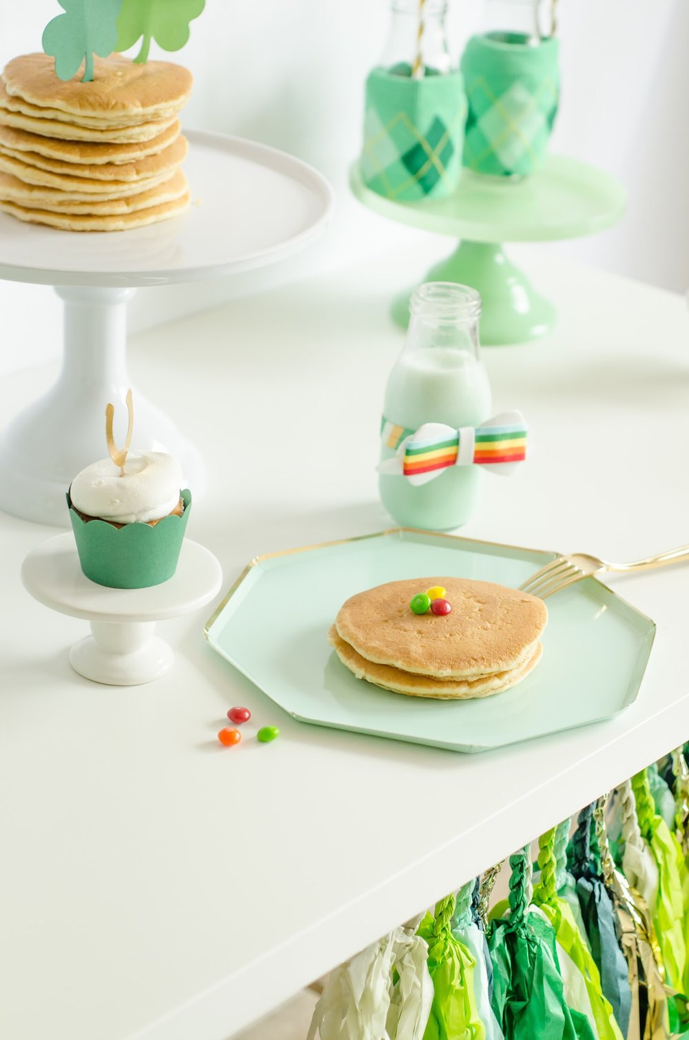 Super cute and easy St. Patrick's Day breakfast idea your kids will love - there's pancakes topped with rainbow candy and of course green milk. Click to see all the green party ideas from Mint Event Design www.minteventdesign.com #partyideas #partydecorations #breakfastfood #saintpatricksday #stpatricksday #pancakes