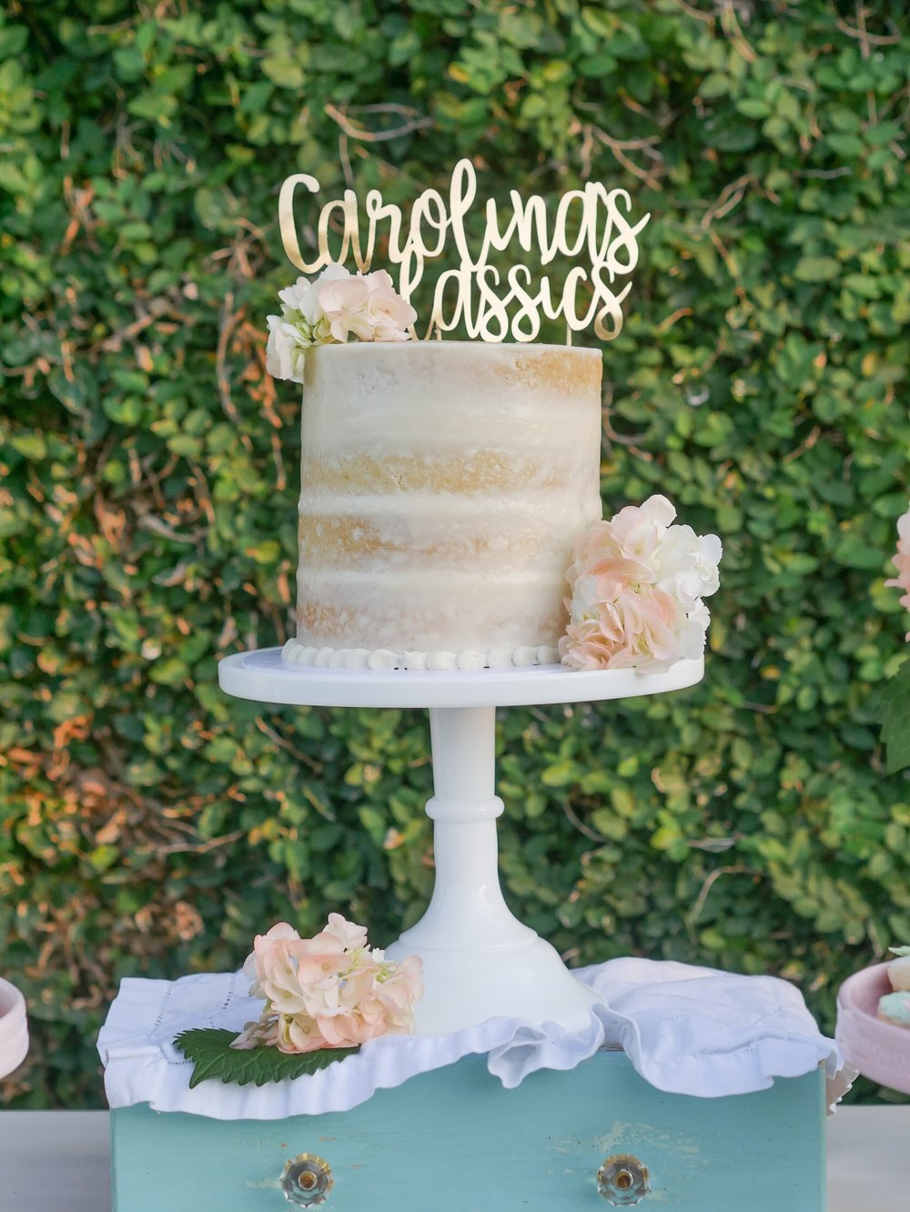 Find out how to set up a garden party with a vintage vibe. Loving this barely frosted party cake with the pretty font cake topper and florals. See how to finish setting up your dessert party outdoors on Mint Event Design www.minteventdesign.com #dessertparty #partytips #partyplanning #partyideas #diyparty #desserttable #outdoorparty #partycake