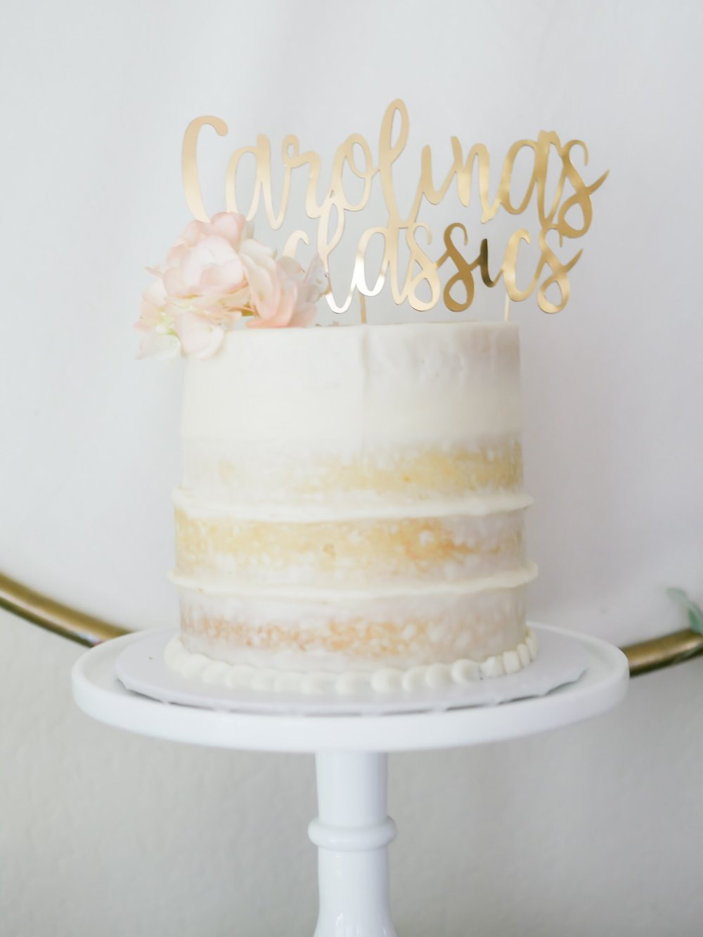 Simple is oh so pretty. A simple barely frosted party cake with a pretty gold topper and a simple floral embellishment makes a huge statement. Click to see all the vintage garden party ideas from Mint Event Design in Austin Texas www.minteventdesign.com #dessertparty #partytips #partyplanning #partyideas #diyparty #desserttable #partycake