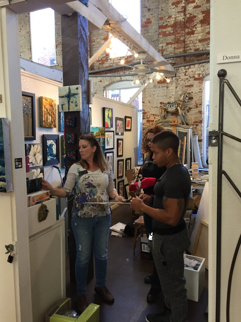 Donna Jassman helping visitors pick out a piece of her work during open studios