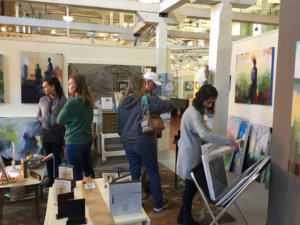 Visitors viewing the work of Gena Brodie Robbins in her corner studio.