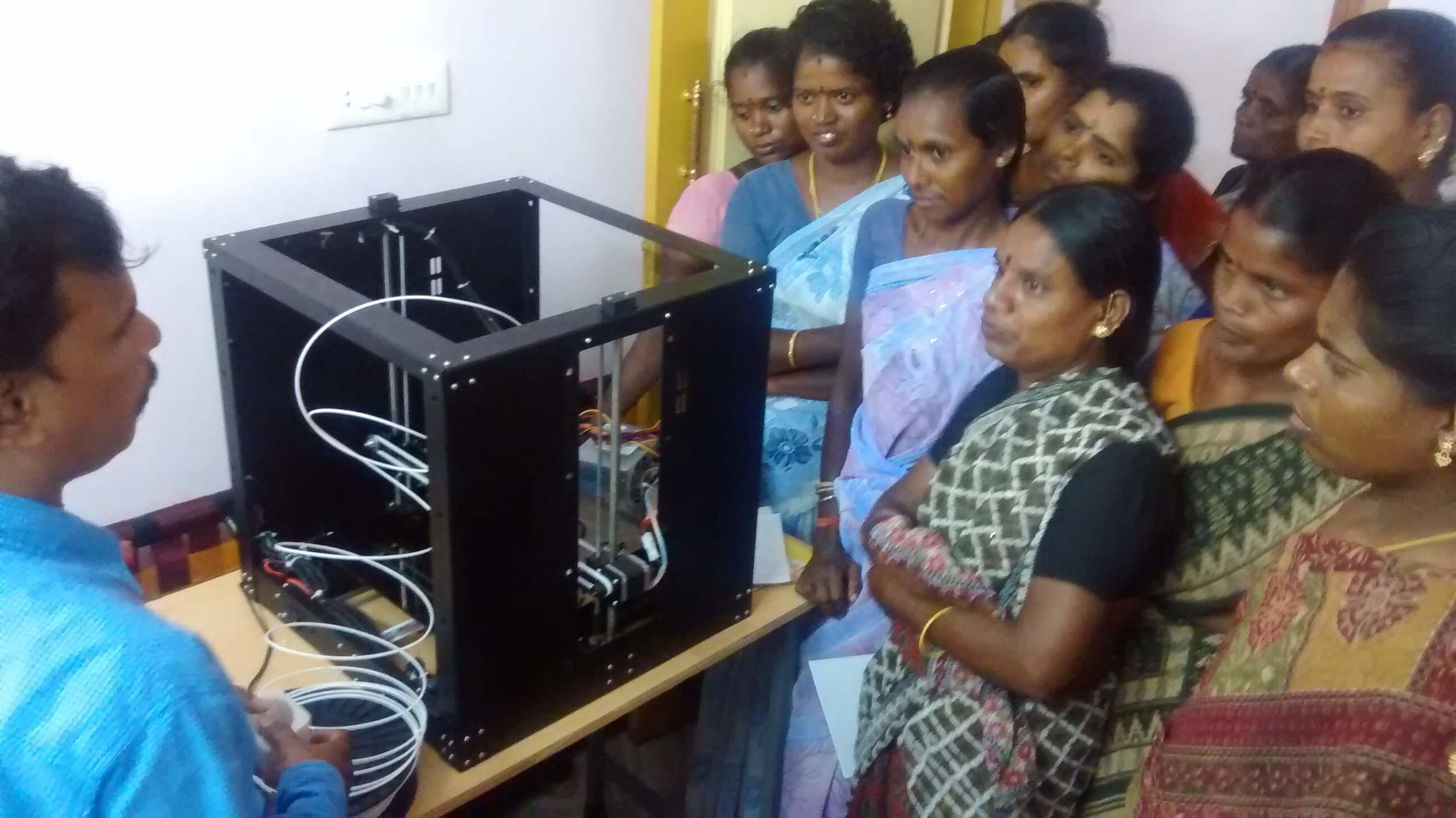 Villagers excited by the 3D printer installed in the village