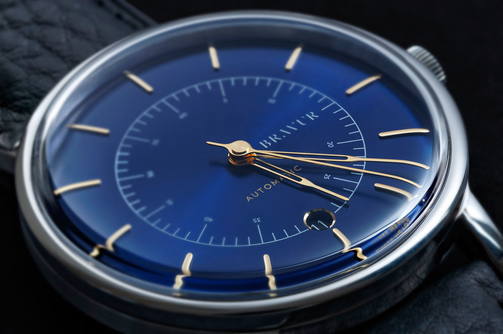 Dial - By using a curved dial, we have been able to make the case slightly slimmer. The minute and second hands are shaped by hand to follow the curvature of the dial.The date window has a discreet chrome frame and is positioned at 6 o'clock.