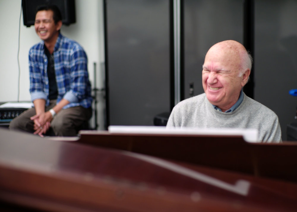 Paul at his piano with Alan, his caregiver, in the background