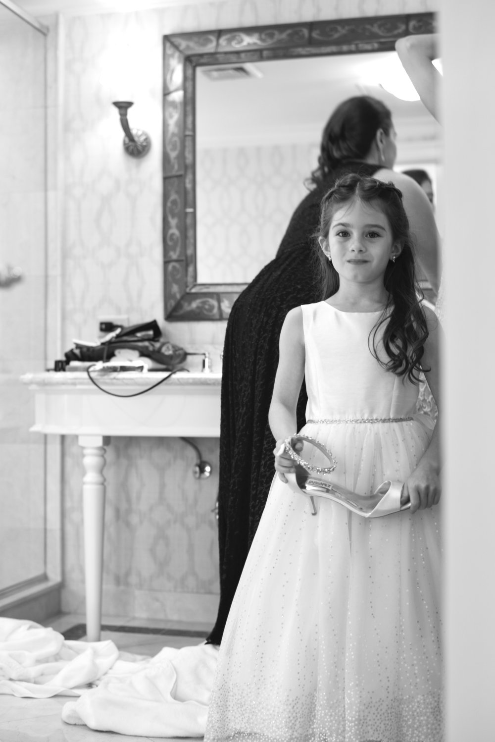 The flower girl, holding the brides shoe, waiting to put it on her foot.