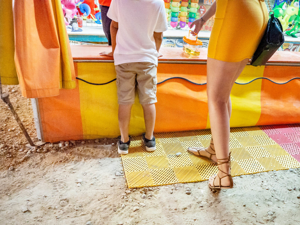 I love the juxtaposition of the young woman's desire to be both a good mom and to feel attractive — as well as the possibility that there might be some tension created between the two when they play out against one another in the form of a slinky dress and uncomfortable footwear on the dusty, gravel midway of a county fair. Yet, … the image contains a child. It also includes a woman — and in what could be interpreted as a sexualized way.