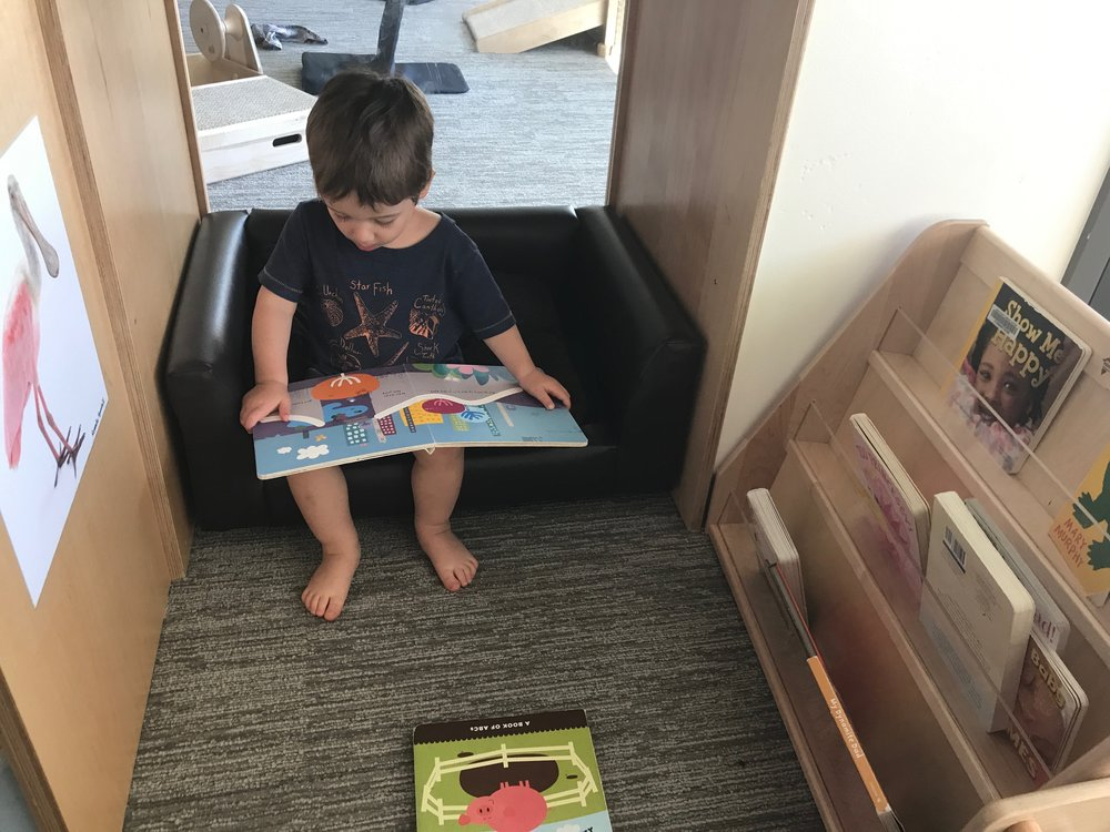 Jackson reading in a window-cubby at daycare. June 30, 2017.