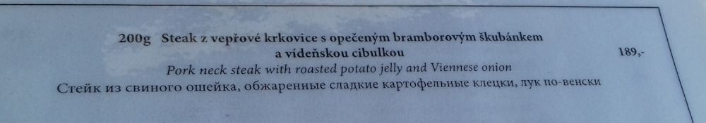 My translation: Pork neck fillet steak with potato cakes and fried onions