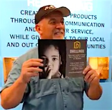 Tom Hackett showing a promotional poster offering free tours of Dwellings homes for tourists in Roatan, Honduras.