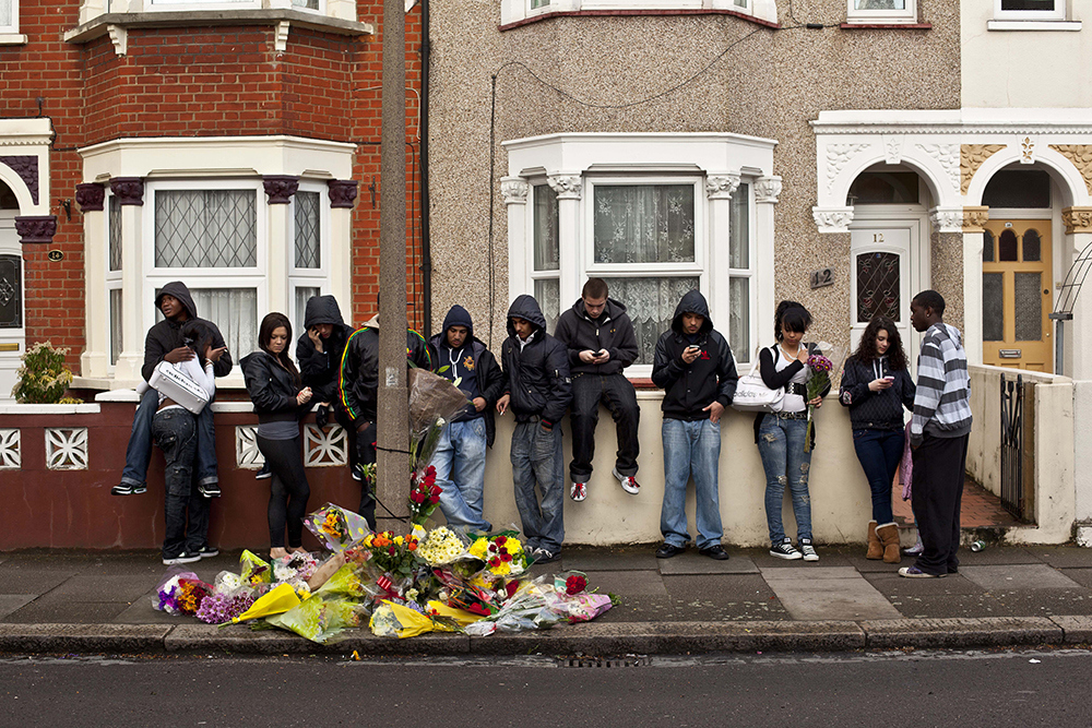 Friends of Negus McClean gather near the spot where he was murdered on Sunday Night. McLean was stabbed to death by a gang of youths on Westminster Road in Edmonton, North London. McLean is the 4th teenager to be stabbed to death in London in 2011.