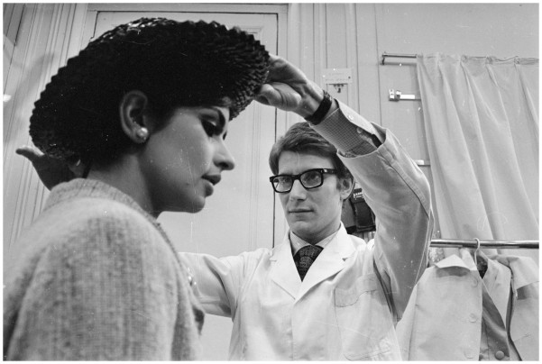 YVES SAINT LAUREN WORKS WITH A FASHION MODEL IN HIS OWN FASHION HOUSE IN PARIS IN 1965.