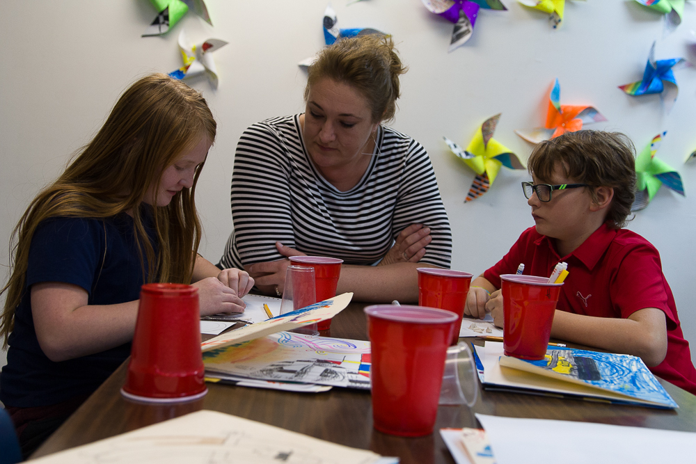 Students work with a teacher on a new art technique.