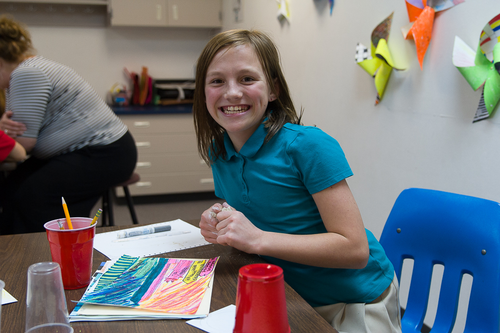 An LCS elementary school student shows her work in project during art class.