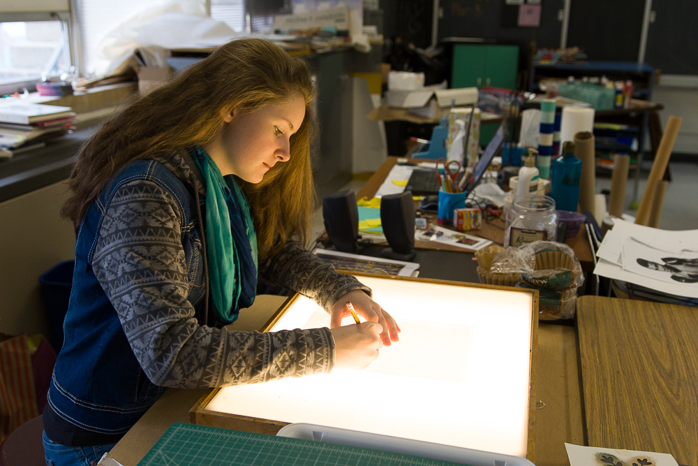 An LCS high school student uses a light board during art class.