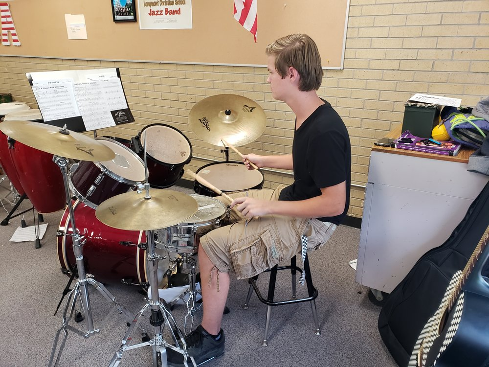 An LCS high school student practices drums for an upcoming concert.