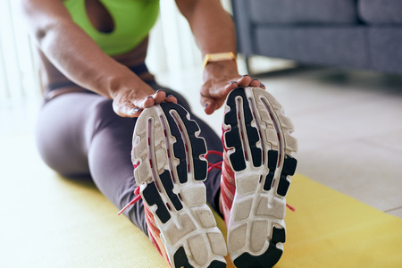 43714845_S_woman_work_out_stretching_african_american_sneakers_hands_exercise.jpg