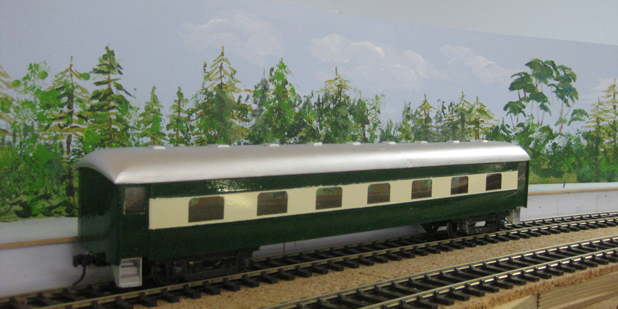 An O-scale carriage in front of the backdrop of trees and sky