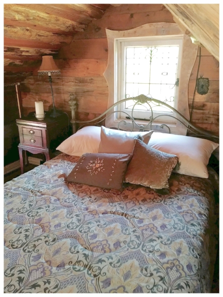 A cozy bed awaits weary travelers in the loft.