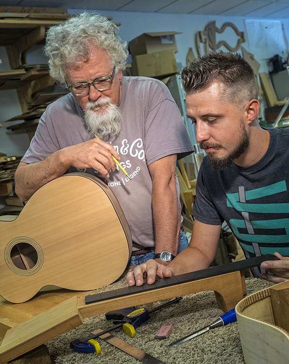 Master Luthier Doug Naselroad and his apprentice, Kris Patrick piece together a guitar neck..