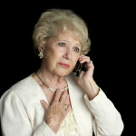 mourning woman speaking on the phone with her hand on her heart