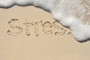 THe word stress written in sand being washed away by waves.