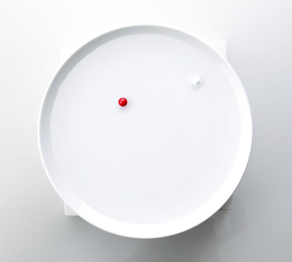 """策展人:我们还需要另一个时钟吗?如果它能让我们内心平和,而不再着急赶路,那么不要犹豫,把它带回家吧。 - 一款小巧的时钟,用户可以自定义时钟面板的材质,选择自己喜欢的钟面玻璃。漂浮在水面上的小球可以显示时间。它由一个陶瓷底座和一对磁球组成。在陶瓷底座表面下方是一对强力磁铁。""""时针和分针""""是两个小球。这些球体具有磁性和浮力,所以如果你将一杯水注入到钟面上,它们能漂浮在水面上,并沿着圆形轨迹移动来显示当前的时间。"""
