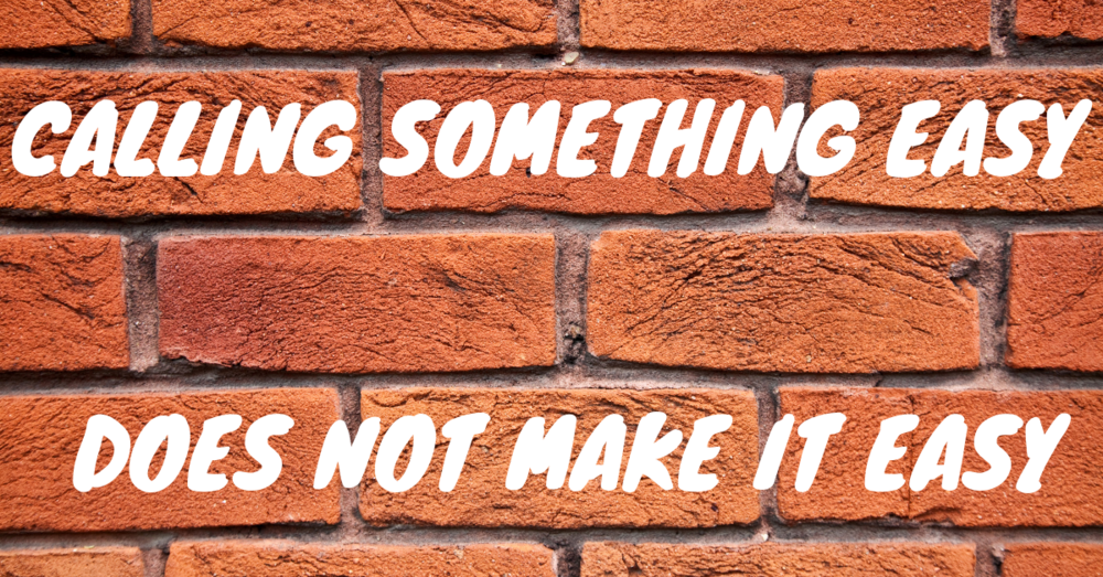 """Calling something easy does not make it easy"" in a graffiti font on a brick wall background."