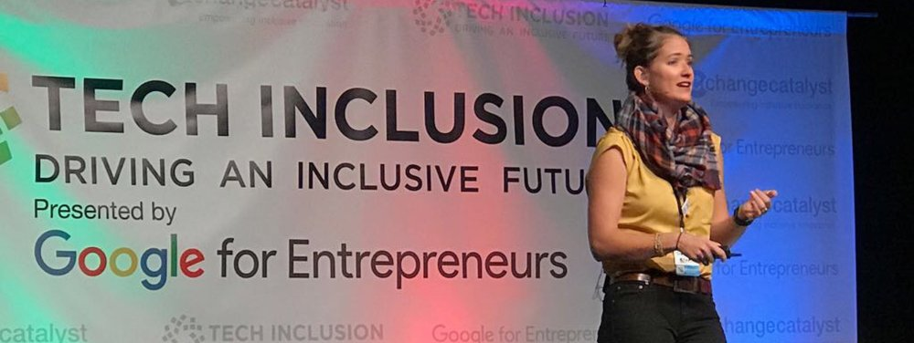 "Liz speaking on stage with a banner behind her that read ""Tech Inclusion."" She is wearing a gold shirt, scarf, and black pants. She has a microphone on her cheek."