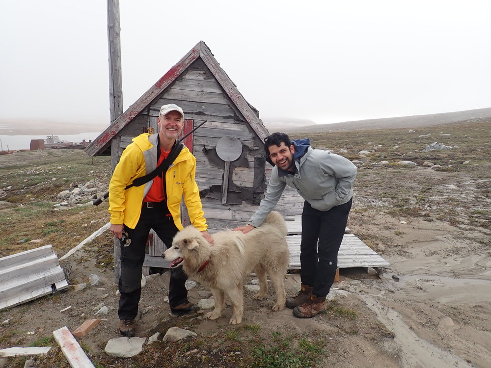 People of the Frontier - meet Hans (yellow jacket), a living legend. He moved here as a kid during the 70's, built the cabin behind him when he was nine years old, and he had a Muskox calf as a pet. He comes back to the Frontier most years and is a major reason why Nyhavn is still usable. Thank you Hans!    Oh and the puppy? A legendary Greenlandic Sled Dog belonging to the Sirius Sled patrol.