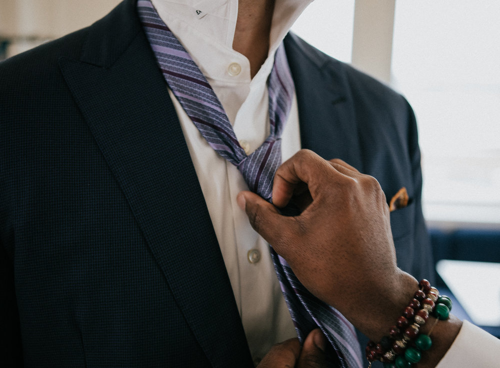 Completing a neck tie knot.