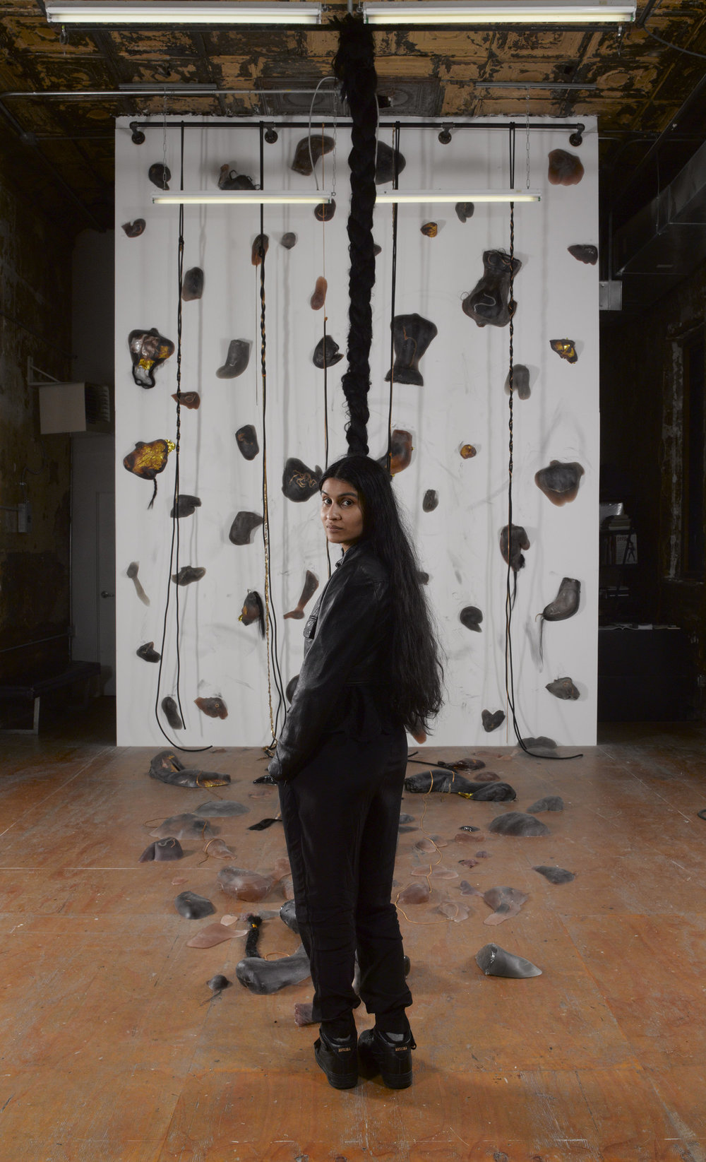 99 Holds , Indoor rock-climbing wall made from 99 unique poured dyed resin casts of the corners of the artist's body. Embedded with wearable Cuban chains, hair, and hypothermia blankets, 120 × 297 in, 2017