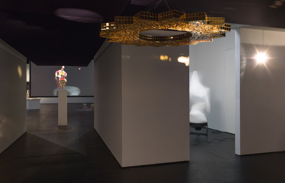[Feat. ], On Whiteness , 2018, at The Kitchen.  The second iteration of the lowered ceiling made from acoustic speaker fabric and wood framing with a black and gold plexiglass chandelier that spins on a disco-motor. The lowered ceiling featured at The Kitchen shares a musical sound track that takes shape from the history of the Glock. The Glock, was a popular civilian gun, because of its safety features, many people bought and traded this gun in the late 80's and the 90's, much music was manufactured from the culture this gun created. Its advent used by NATO, however the United State went with the Barrette, a clunky and hard to use weapon, that most police officers, especially rookies fail to use correctly. The Glock, mostly a light weight plastic gun, was misrepresented as a dangerous weapon in the US, popularize by Bruce Willis in the movie Die Hard 2, was actually effective, safe, and used by most every other country on the list of NATO as official arms.