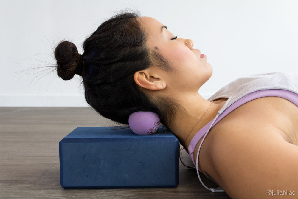 Place the suboccipitals (where the base of your skull meets the back of your neck) VERY gently along the middle of the two balls. Subtly roll your head from left to right.