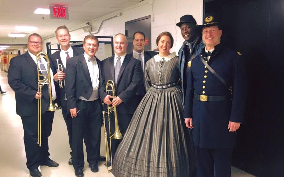 Members of the brass section with conductor Dante Santiago Anzolini and members of the cast of Appomattox