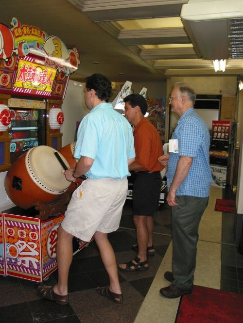 Bass section playing a drumming game at a Japanese arcade in Shinjuku