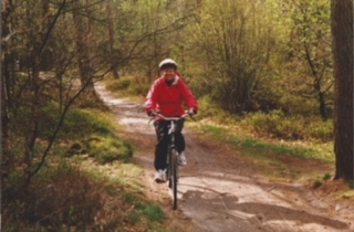 Photo of Meg biking in the forest -- Netherlands