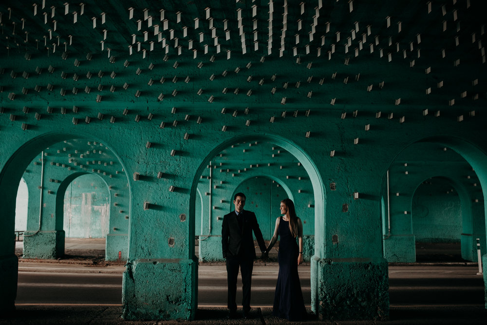 Couple standing under teal Cass Ave Underpass in Detroit, Michigan