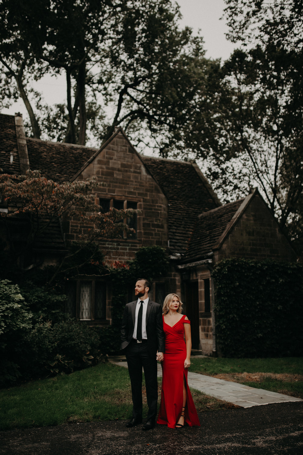 Couple wearing red dress standing at Edsel & Eleanor Ford Mansion