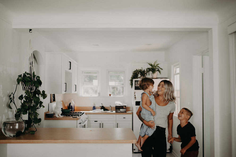 Mom and two sons laughing and standing in a white kitchen