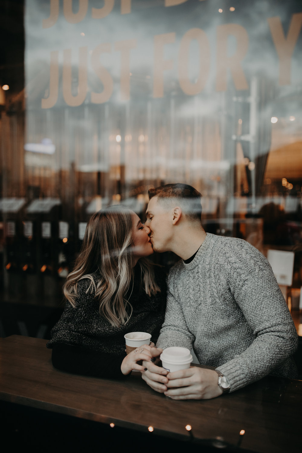 Couple kissing and holding coffee at Roasting Plant in Detroit