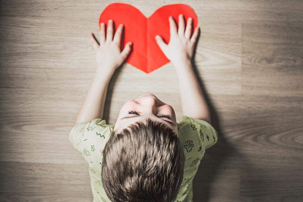 little boy holding a paper heart