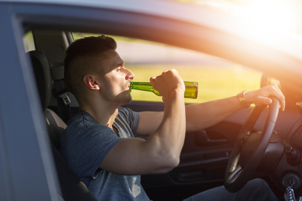 A man drinking alcohol with holding the car steering