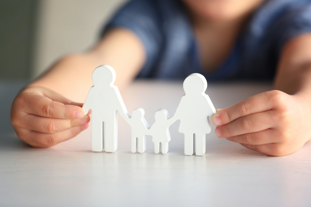 Child holding figure in shape of happy family