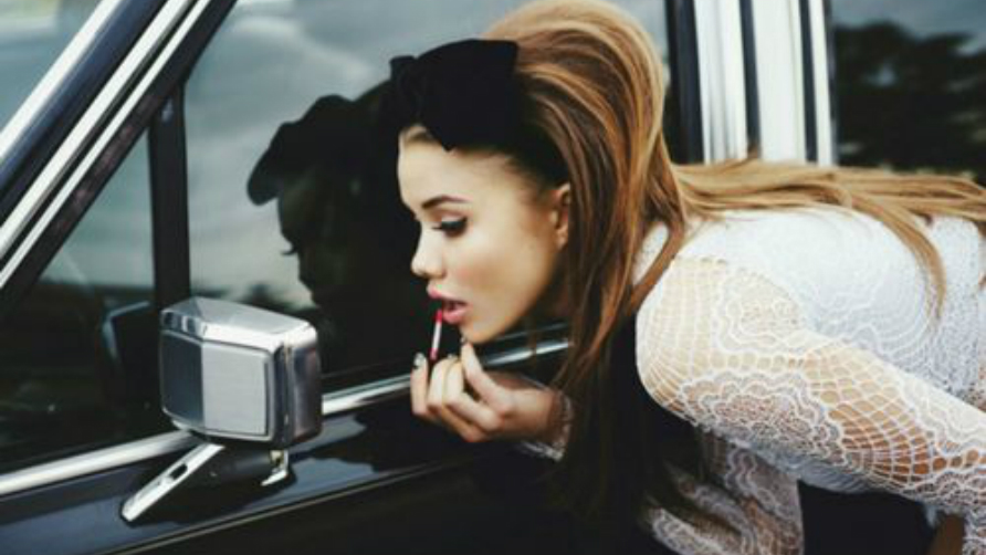 girl-looking-at-a-rearview-mirror-and-putting-a-lipgloss-on.jpg