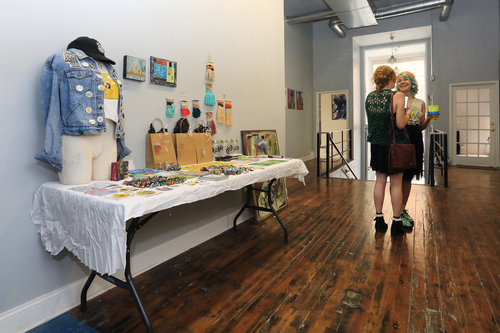 """Artists Laura Little (left) and Alecia Vera Buckles (right) standing by the """" Swag """" table at OFFLINE.   Artists were encouraged to produce miniatures in the style of their typical work to encourage sales and generate hype for the show."""