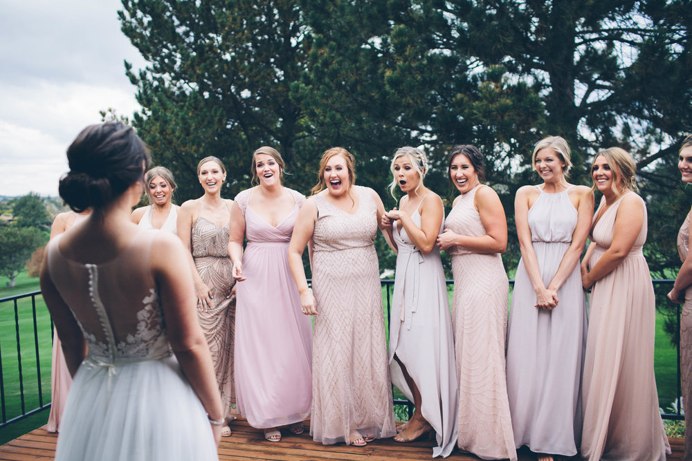 bride revealing the gown to bridesmaids