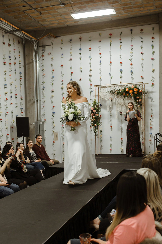 spokane wedding dress fashion show off shoulders runway model white flowers