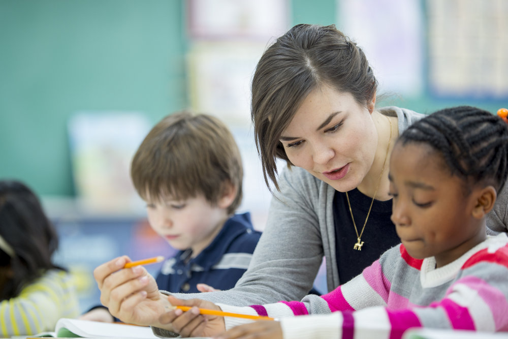 Teacher-Helping-a-Student-Understand-an-Assignment-507749622_4465x2977.jpeg